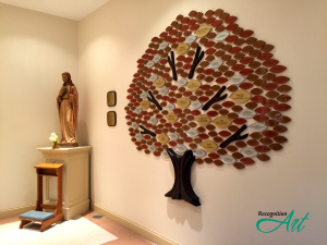 A sculpted wood donor recognition tree with Plexiglas leaves in earth tones categorized by size.